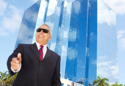 Smiling business man in front of glass offices